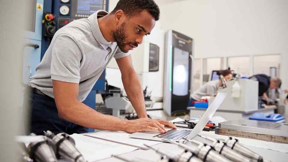 homem em computador na fábrica