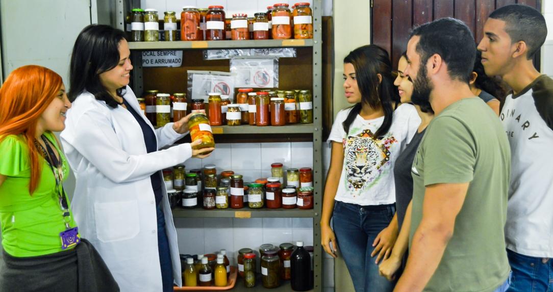 estudantes com professora em torno de armário com diversas conservas em vidros