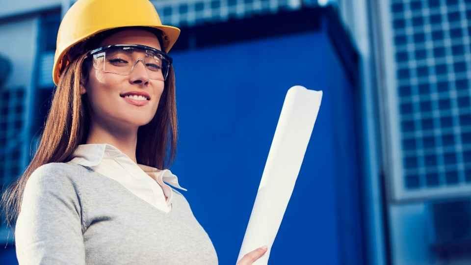 mulher de capacete e planta de projeto na mão
