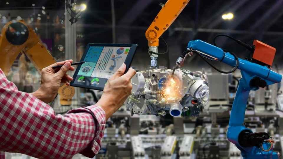 mãos segurando tablet em frente a um robô