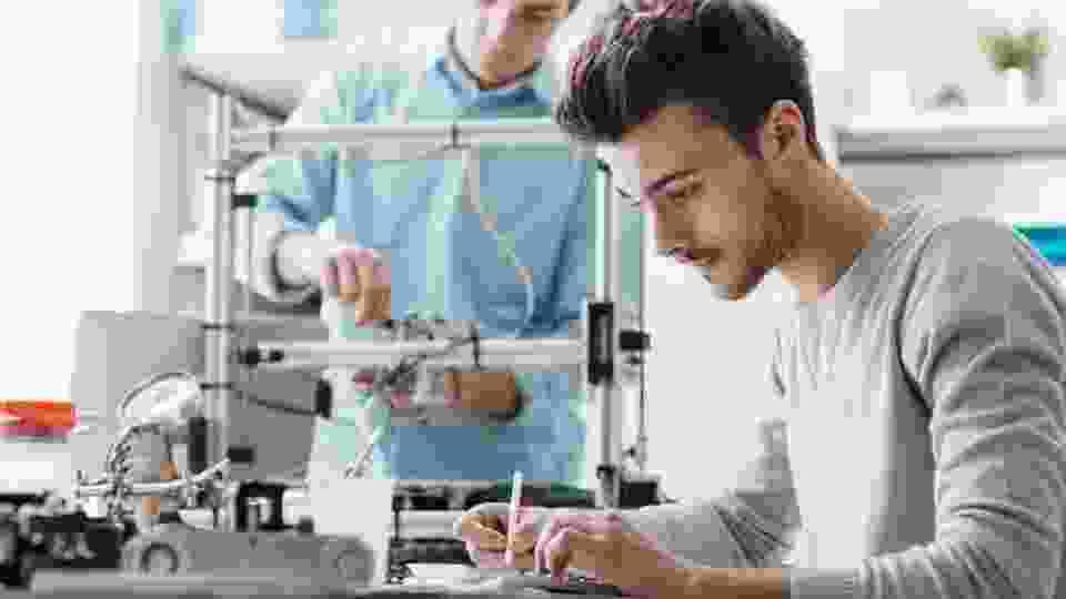 rapazes em laboratório com impressora 3D