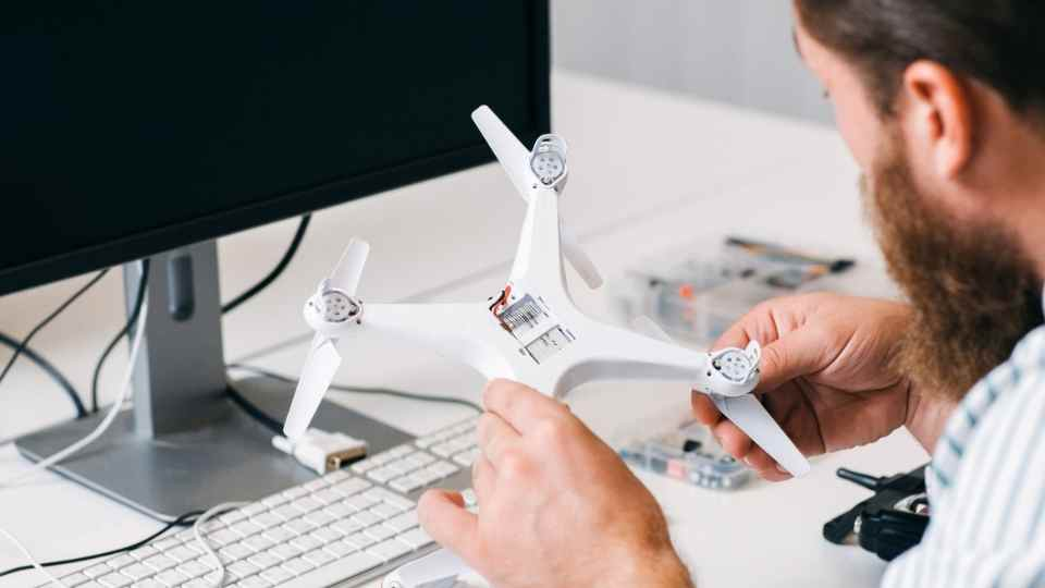 rapaz manuseando drone e computador