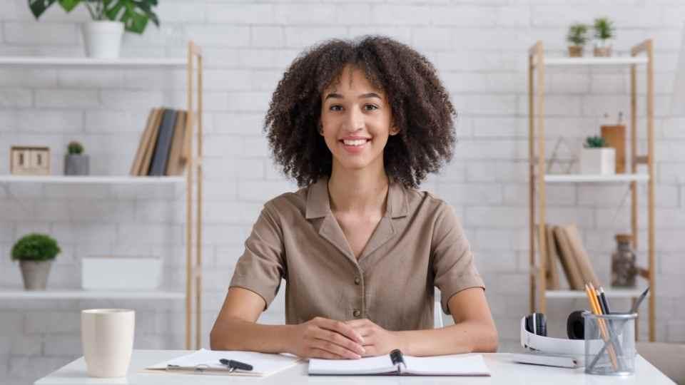 mulher em mesa com livro e fone de ouvido